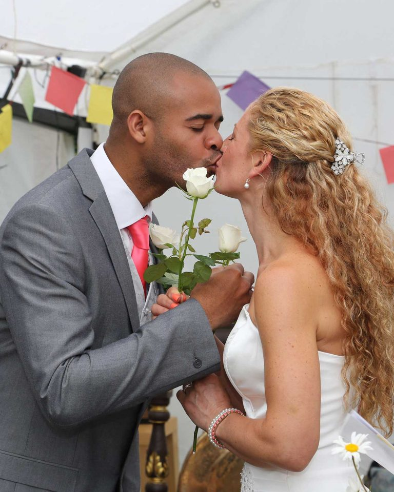 Wedding-lovine-kiss-bride-and-groom-each-holding-a-white-rose-Lloyd-Dunkley-Photography-0L8A7571