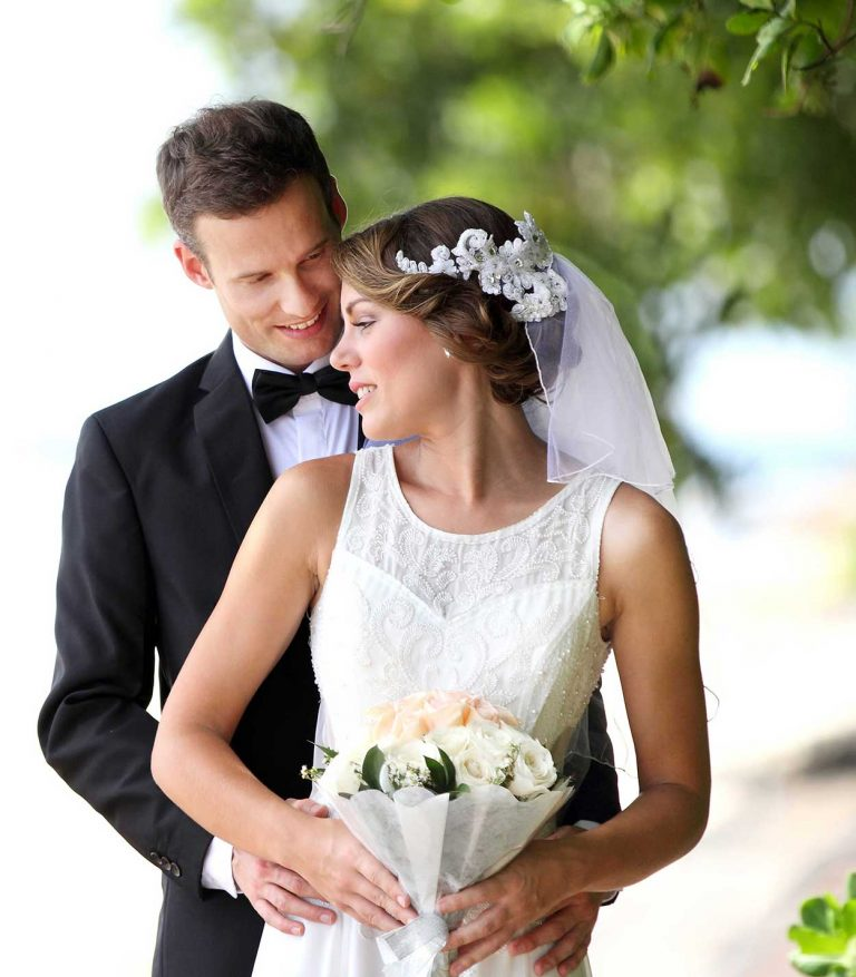 Wedding-bride-and-groom-embracing-holding-flowers-Lloyd-Dunkley-Photography-39402824