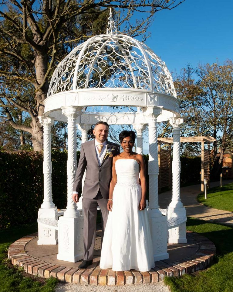 Wedding-the-bride-and-groom-standing-by-the-gazebo-Lloyd-Dunkley-Photography-DSCF3487
